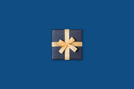 Holiday card. Grey gift box with gold bow on classic blue background. Flat lay, top view, copy space.