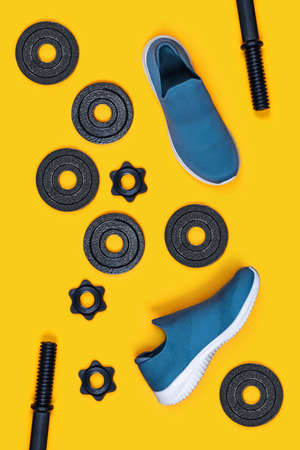 Sports vertical background. Dumbbells and Sneakers on yellow background. Flat lay, top view, copy space. Stockfoto