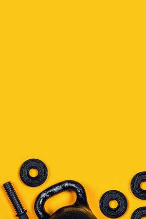 Sports vertical picture. Kettlebell and dumbbell on yellow background. Flat lay, top view, copy space.