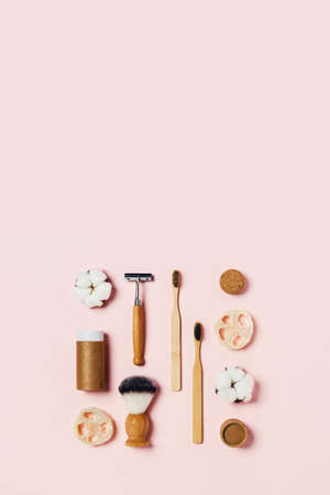 Zero waste concept. Natural bamboo toothbrush, bamboo ear sticks, razor, paper tube, wooden drinking tube, natural sponge on pink background. Flat lay, top view, copy space.
