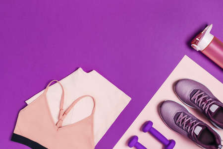 Sports equipment and shoes for womens training. Pink-purple background, diagonal composition.