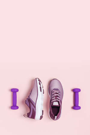 Sports dumbbells and shoes for womens training. Pink background, vertical picture. Flat lay, top view, copy space.