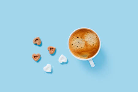 Morning cup of strong coffee with five pieces of sugar in the shape of hearts on blue background.