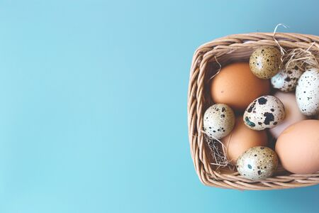 wicker basket with quail and compartment eggs on a gray background. happy easter.