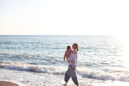 mom and daughter are playing on the sandy beach.
