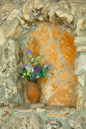 antique vase with wildflowers in a stone arch. 스톡 콘텐츠