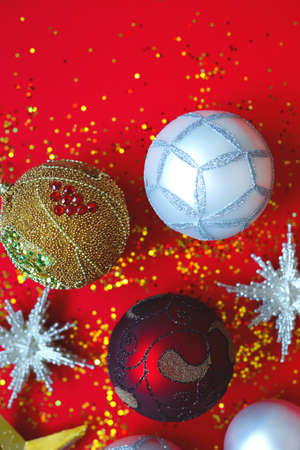 Beautiful Christmas balls and stars on a red background with sparkles.