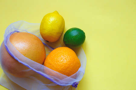 juicy ripe citrus fruits in an eco-friendly shopping bag.