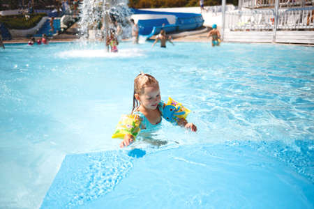 little girl swims in the pool in the outdoor water park