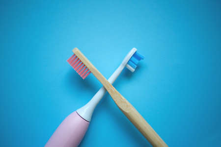 two ultrasonic electric toothbrushes on a blue background.