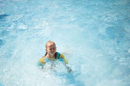 little girl swims in the pool in the outdoor water park.