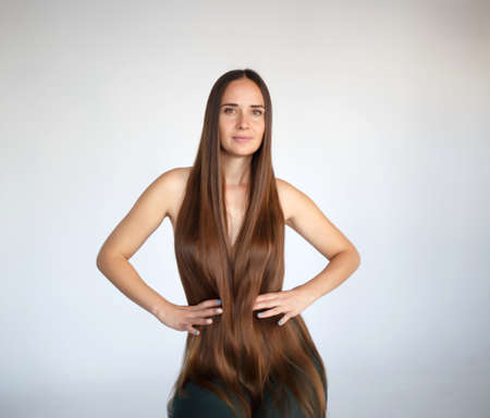 young beautiful woman with very long hair sits on a chair.