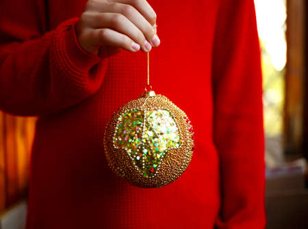 christmas tree decoration golden ball in hand.