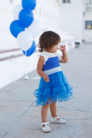 little girl in a beautiful dress with a huge fountain of balloons