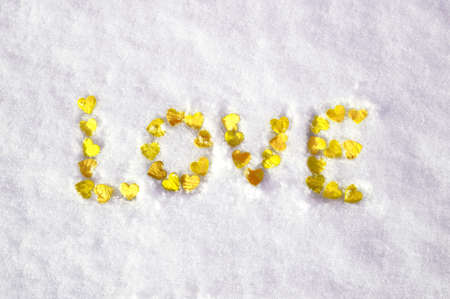 valentine's day concept: word love laid out with hearts on snow. Standard-Bild