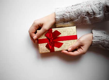 双手握着白色背景上的礼物。