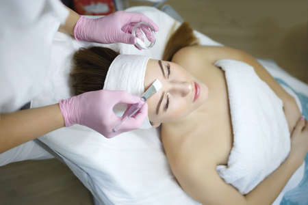 Cosmetologist does face peeling of a beautiful woman. Women's cosmetology in the beauty salon.