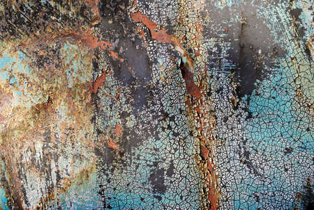 crackles: Rusty colored metal surface with turquoise cracked paint