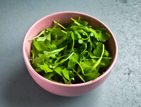 Salad of fresh arugula in a pink bowl on a gray table