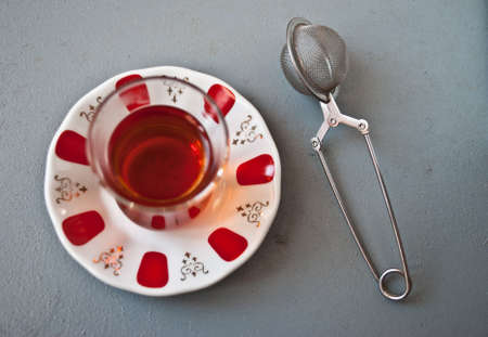 amasing: Turkish tea in traditional glass and empty tea strainer on a gray background. Top view Stock Photo