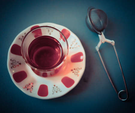 amasing: Turkish tea in traditional glass and tea strainer on a dark blue background. Top view