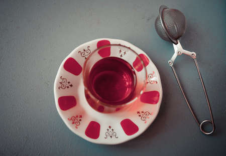 amasing: Turkish tea in traditional glass and tea strainer on a gray background. Top view Stock Photo
