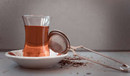 amasing: Turkish tea in traditional glass and tea strainer in a pile of tea leaves on a light gray background. Toned image Stock Photo