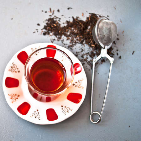 amasing: Turkish tea in traditional glass and tea strainer in a pile of tea leaves on a light gray background. Top view Stock Photo