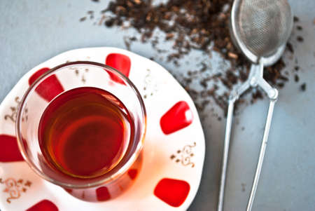 amasing: Turkish tea in traditional glass and tea strainer in a pile of tea leaves on a light gray background. Top view. Close up Stock Photo