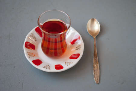 amasing: Turkish tea in traditional glass with spoon on a gray background Stock Photo