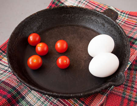 cast iron red: Old cast iron frying pan on red cotton towel, cherry tomatoes and eggs
