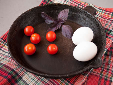 cast iron red: Old cast iron frying pan on red cotton towel, cherry tomatoes, eggs and basil leaves