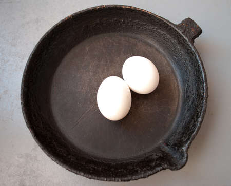 Old cast iron frying pan and eggs. Top view