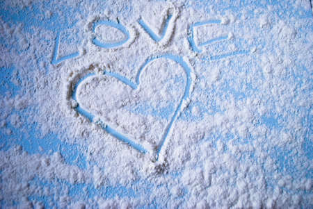 love image: Image of the heart and an inscription love on a scattered flour on a light blue surface