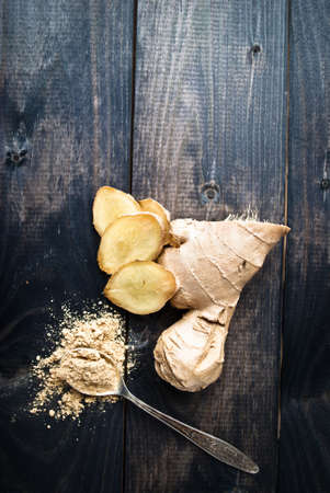 Fresh ginger root and spoon with dry ginger on shabby rustic wooden background