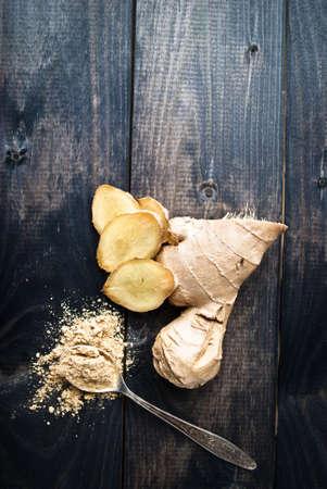 planta con raiz: ra�z de jengibre fresco y cuchara con jengibre seco en el fondo de madera r�stica en mal estado Foto de archivo