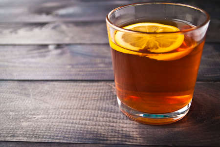 Zitronenscheibe in einer Schale schwarzer Tee auf hölzernem Hintergrund