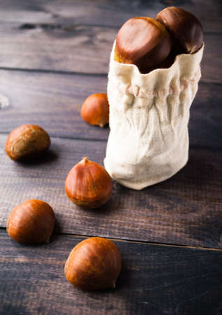 raw cotton: Full cotton bag of raw chestnuts on rustic wooden background