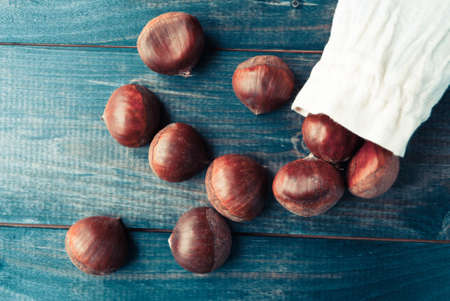 raw cotton: Raw chestnuts in cotton bag on dark turquoise shabby wooden background Stock Photo