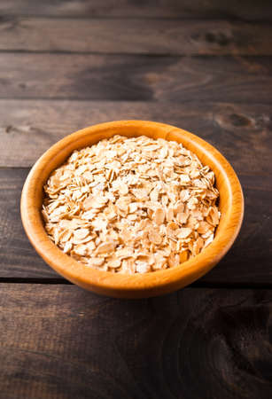 rolled oats: Raw rolled oats in bowl on brown wooden surface Stock Photo