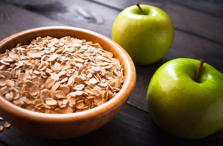 avena en hojuelas: Rolled oats in bowl and green apples on wooden surface