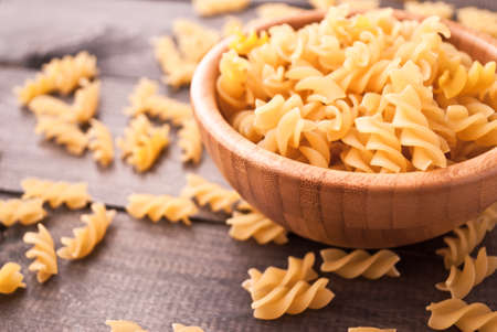rotini: Raw pasta on wooden background and bamboo bowl of pasta
