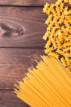 wooden surface: Two kind of raw pasta on rustic wooden surface as a background Stock Photo
