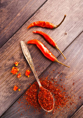 raw tea: Full tea spoon of ground chili pepper, three whole raw bright red chilies and some slices on wooden background Stock Photo
