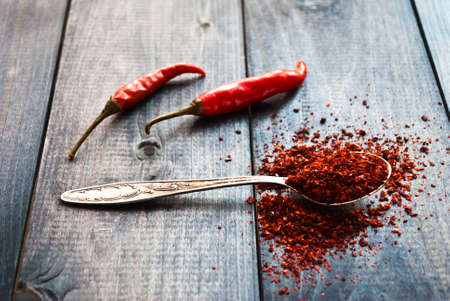 raw tea: Full tea spoon of ground chili pepper and whole raw red chilies on wooden background