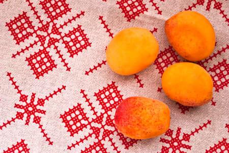 Gruppe von rohem Aprikosen auf einem Küchentuch mit rotem Muster