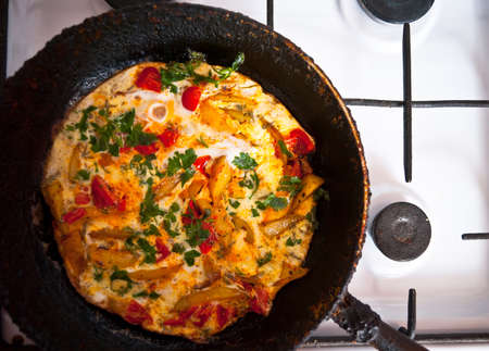 old gas stove: Homemade fritatta with tomatoes, parsley and fried potato in the old cast iron frying pan and on the gas stove Stock Photo