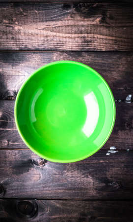 Empty bright green soup plate on a broun rustic wooden background