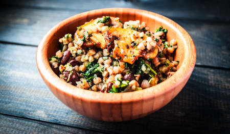 Bamboo bowl of boiled buckwheat with spinach and red beans with slices of fried champignon on the top, menu page Stock Photo