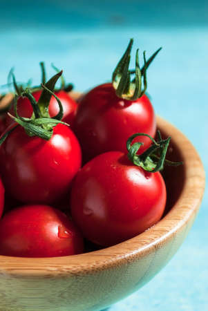 Ripe red cherry tomatoes in a bowl on a turquoise wooden table. Close up 写真素材